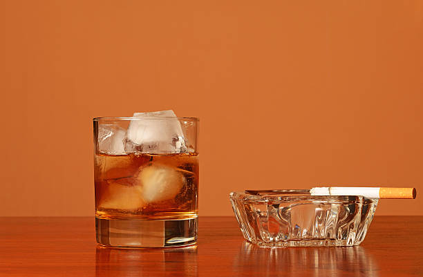 Glass of wiskey on the rocks and ashtray with cigarette stock photo