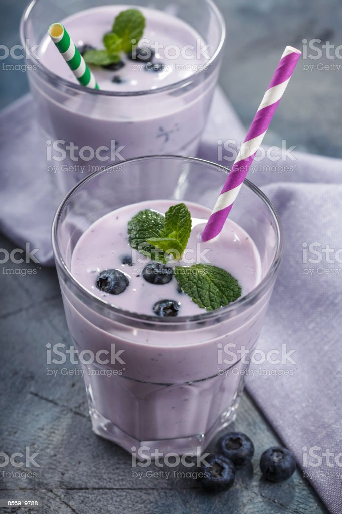 Glass of yogurt with blueberries and mint leaves stock photo