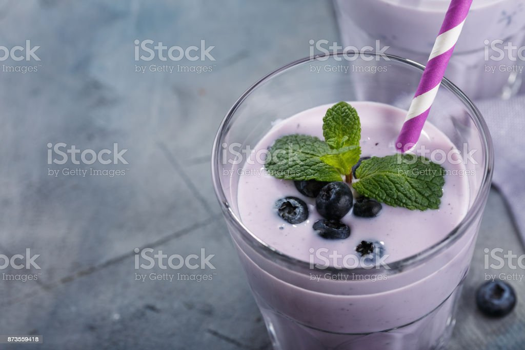 Glass of yogurt with blueberries and mint leaves with space for text, close-up stock photo