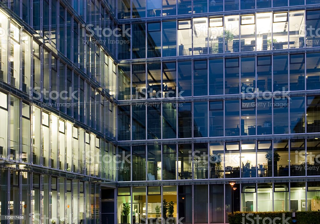 Glass office building with the lights turned on stock photo