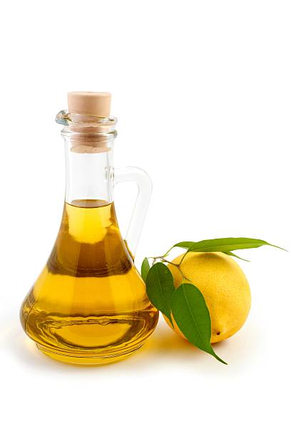 Glass oil pitcher and a lemon with leaf attached stock photo
