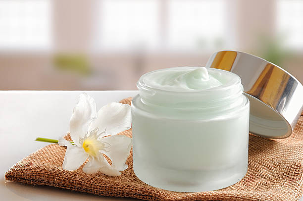 Glass open jar with cream on burlap stock photo