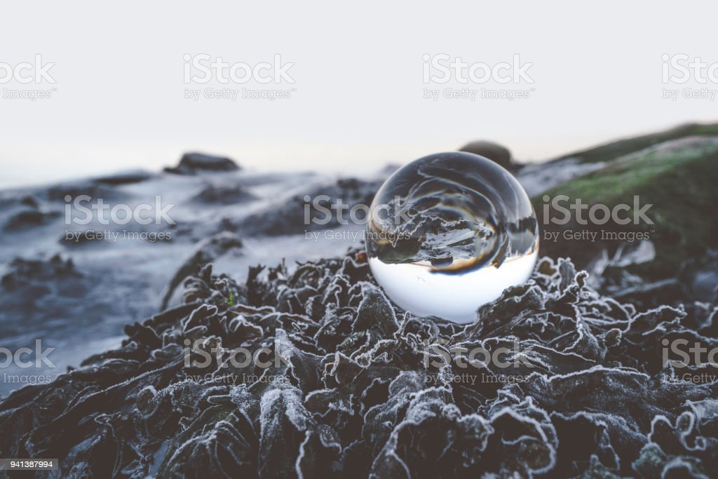 Glass orb on frozen leaves in the winter stock photo