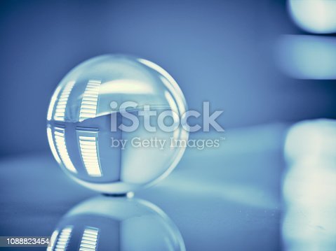 A blue color toned clear glass sphere in a home interior.