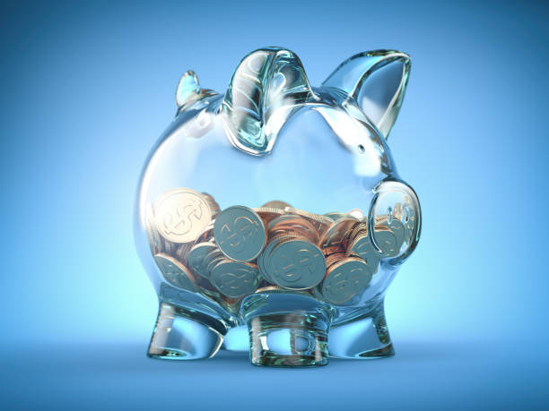 Glass piggy bank and coins with dollar sign on blue background. Deposit, savings money and investment concept. stock photo