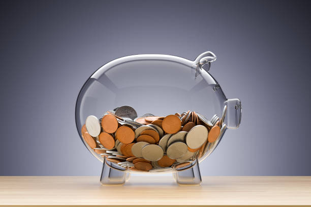 Glass piggy bank with coins stock photo