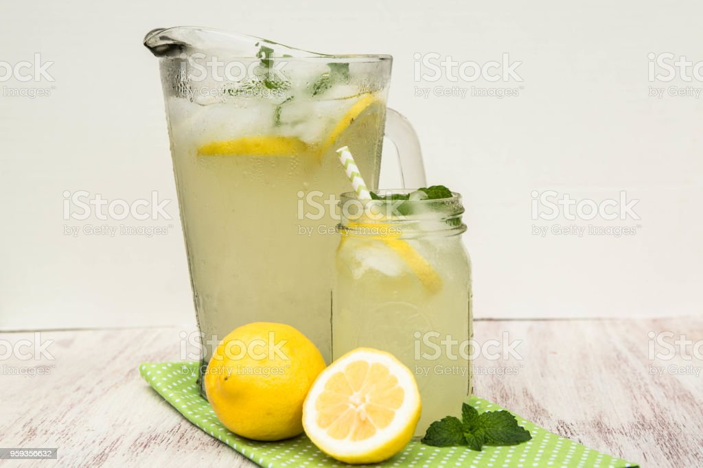 Glass Pitcher and Mug of Lemonade On White Background stock photo