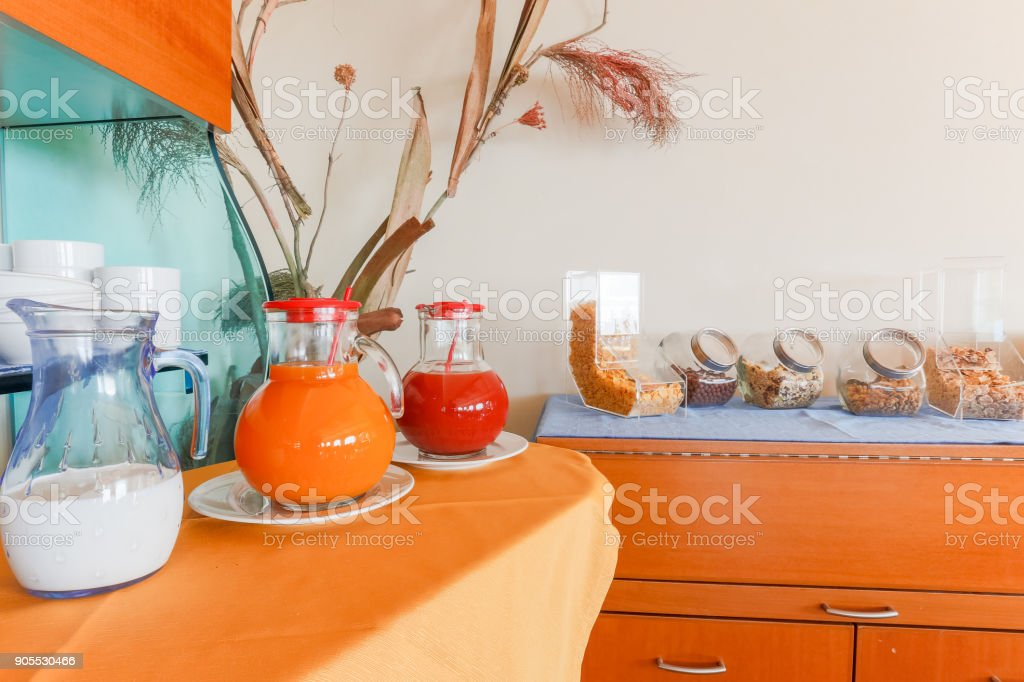 Glass pitchers with milk, juice and assorted cereals stock photo