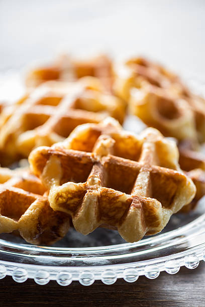 Glass Plate of Mini Belgium Liege Waffles on Wood Table Closeup view of freshly made bite sized, small Belgium Liege waffles on a clear, decorative glass plate set on a wooden table. lulik stock pictures, royalty-free photos & images