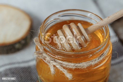 istock Glass pot of honey on a rustic bacground. 690291682