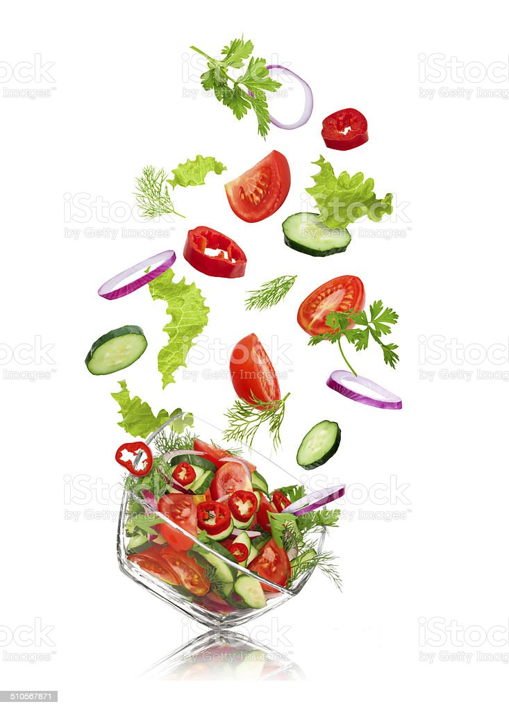 glass salad bowl in flight with vegetables stock photo