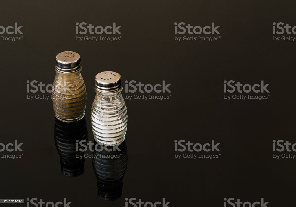 Glass salt and pepper shakers on black background stock photo