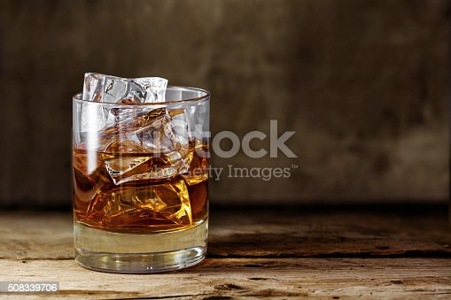 istock glass scotch whiskey with ice on a rustic wooden table 508339706