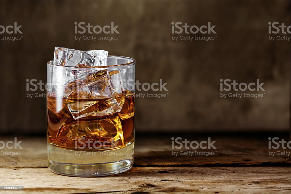 glass scotch whiskey with ice on a rustic wooden table stock photo