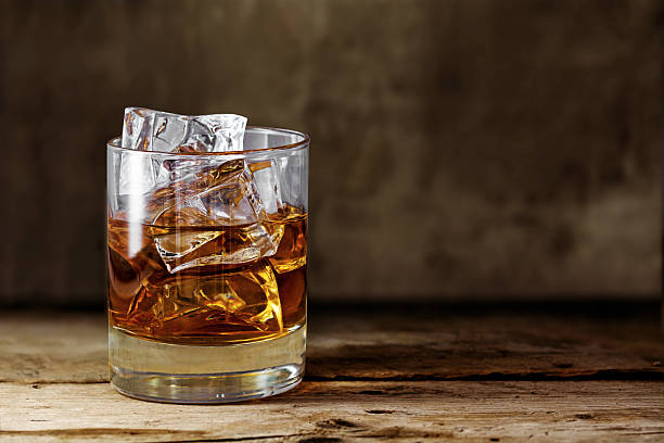 glass scotch whiskey with ice on a rustic wooden table - whiskey stock photos and pictures