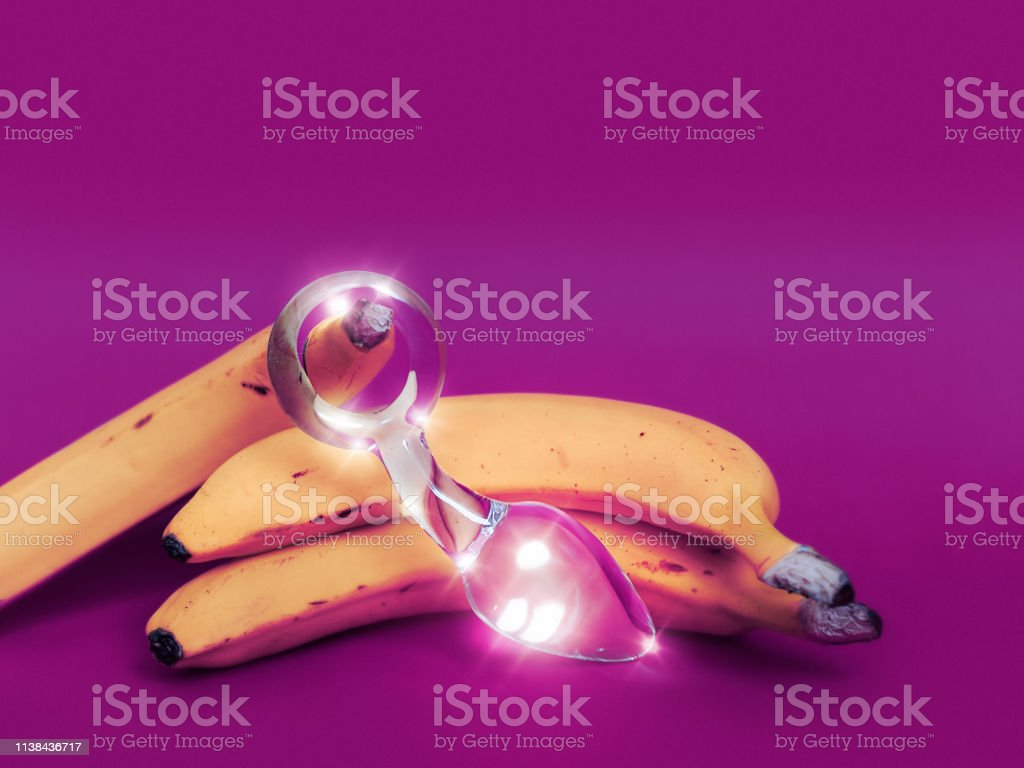 Glass sex toy and a yellow banana are on a colored background There is an empty space for the text. Image is suitable for sex shop advertising Abstract Stock Photo