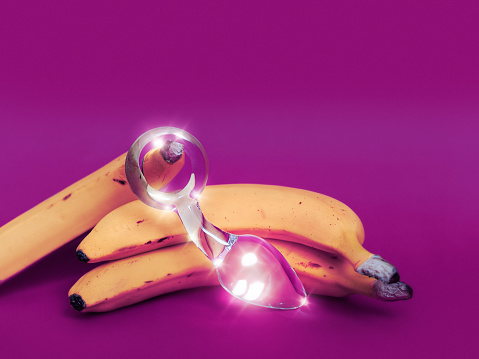 Glass Sex Toy And A Yellow Banana Are On A Colored Background Stock Photo - Download Image Now