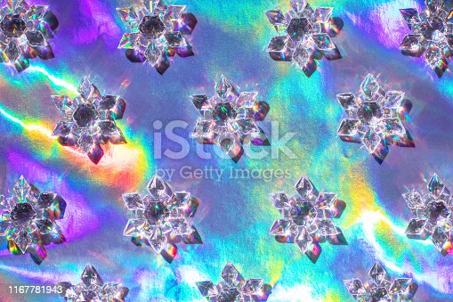 Clear glass snowflakes laying diagonally on bright holographic background. Trendy sunlight christmas photo pattern. Open composition. Flat lay style.