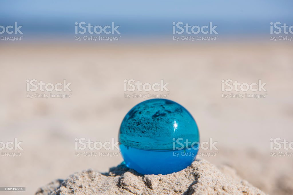 Glass sphere at the beach. Sunny summer day.