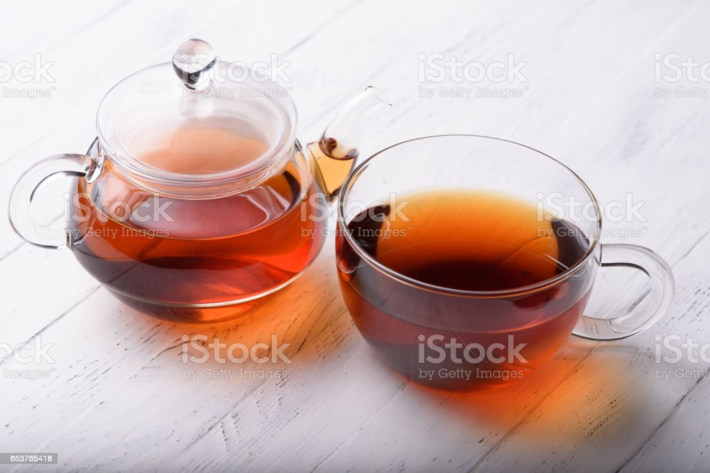 Glass teapot and cup with hot black tea - foto stock