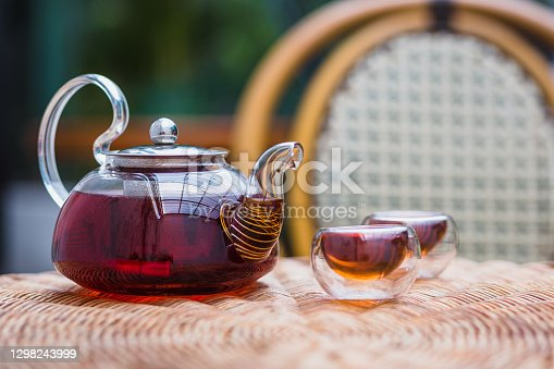 A glass teapot and tea cups on rattan table at home, Tea ceremony concept