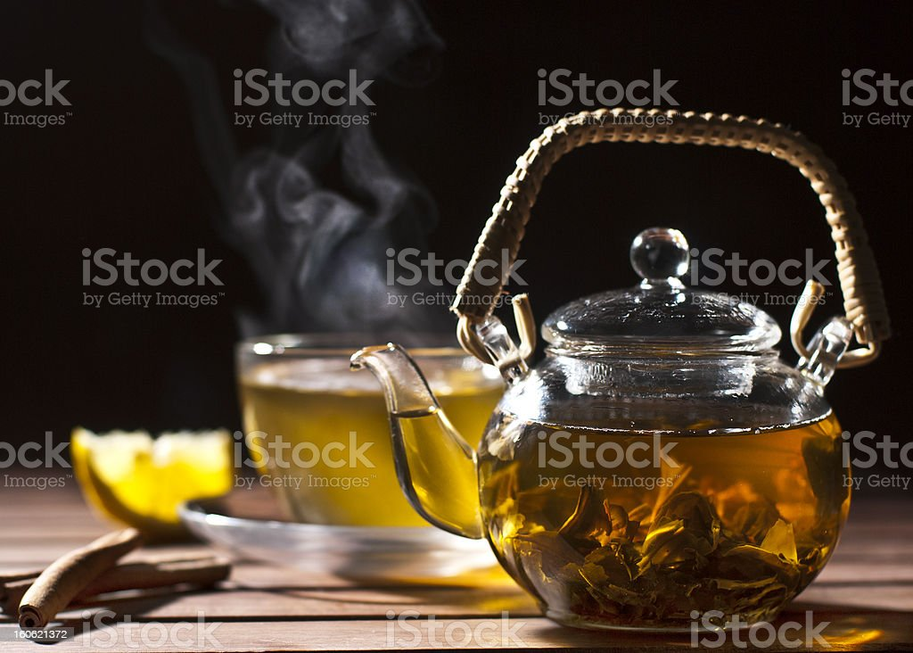Glass teapot filled with tea sitting on a table with a cup stock photo