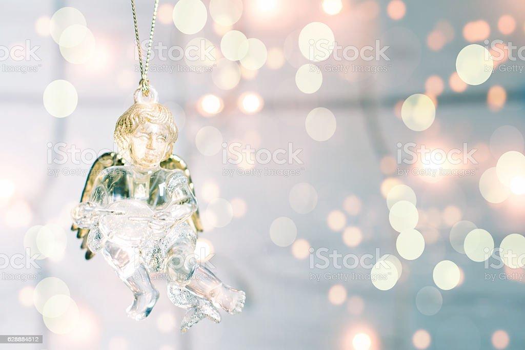 Glass toy Christmas Angel on a golgen bokeh background stock photo