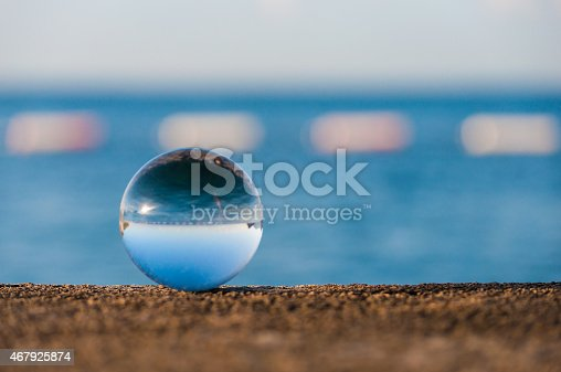istock Glass transparent ball on sea background and grainy surface. Water 467925874