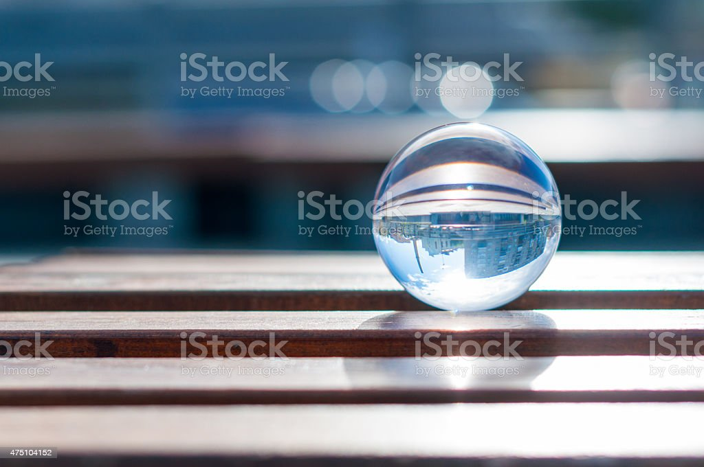 Glass transparent ball on wooden slats background. With empty space stock photo