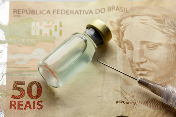 """Glass vaccine bottle with liquid and syringe needle over a brazilian """"50 Reais"""" bank note from close stock photo"""