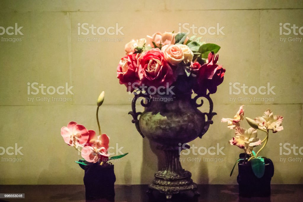 Glass vase and flowers decoration with spotlight. Hotel room...