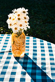 A glass jar vase filled with lemon slices and daisies sitting on a picnic table and casting a shadow at sunset.
