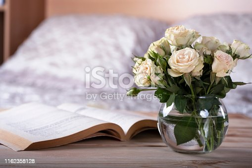 Glass vase with roses and book on bedside table in light cozy bedroom interior. Selective focus.