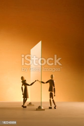 Two wooden figures reach out to touch each other through a glass Wall.These are unique and original wooden figures with accessories crafted by the photographer from recycled materials.  All the items in this image are carefully hand crafted and owned by the photographer