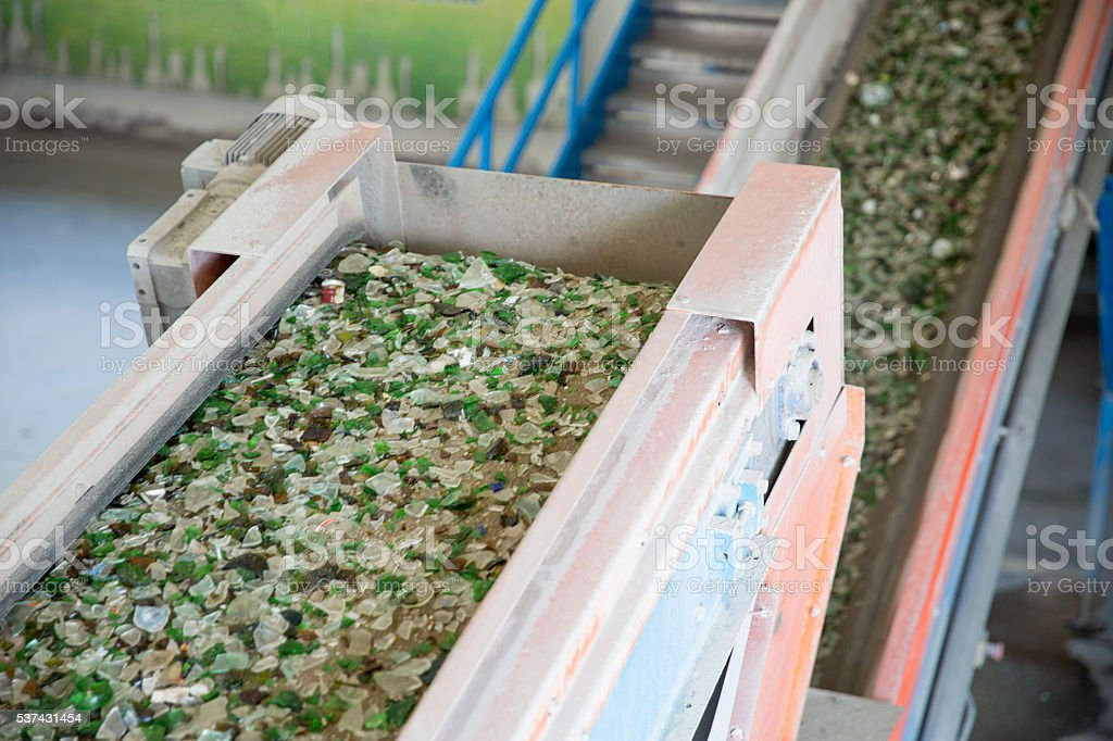 Glass waste in recycling facility. Glass particles in a machine stock photo