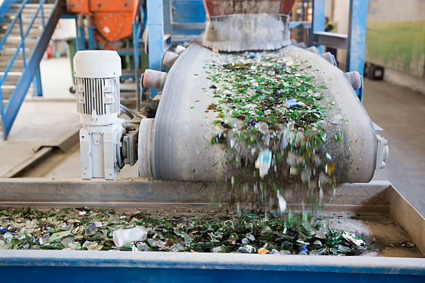 Glass waste in recycling facility. Glass particles Glass particles for recycling in a machine in a recycling facility. Different glass packaging bottle waste. Glass waste management. Glass recycling is the process of waste glass into usable products. bottle bank stock pictures, royalty-free photos & images
