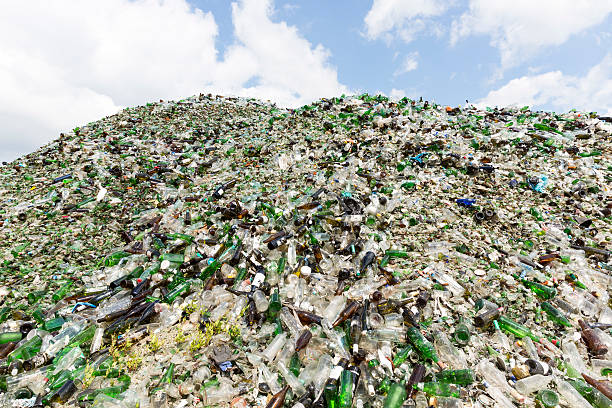 Glass waste in recycling facility. Pile of bottles. Glass waste for recycling in a recycling facility. Different glass packaging bottle waste. Glass waste management. Process of waste glass into usable products. Pile of  different bottles. bottle bank stock pictures, royalty-free photos & images