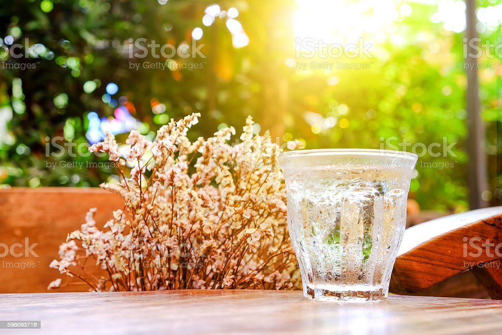 Glass water on wooden table with dry flower background. royalty-free stock photo
