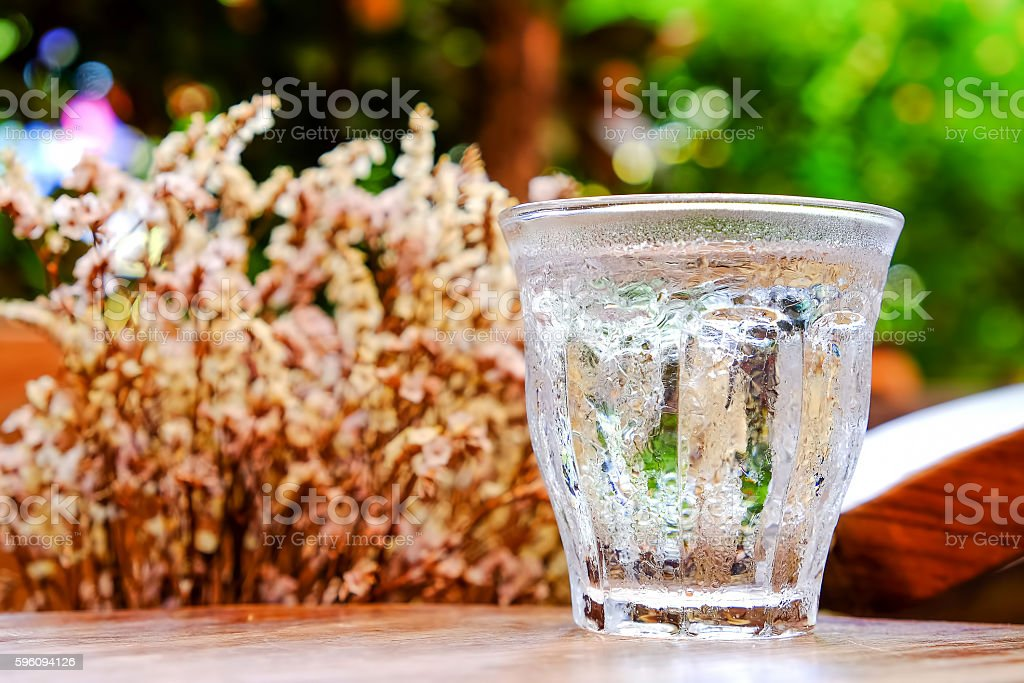 Glass water on wooden table with dry flower background.Focus on royalty-free stock photo