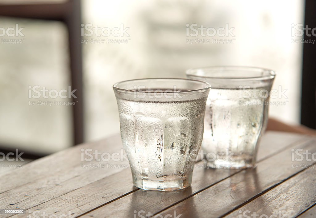 Glass water on wooden table with poor light background. Lizenzfreies stock-foto