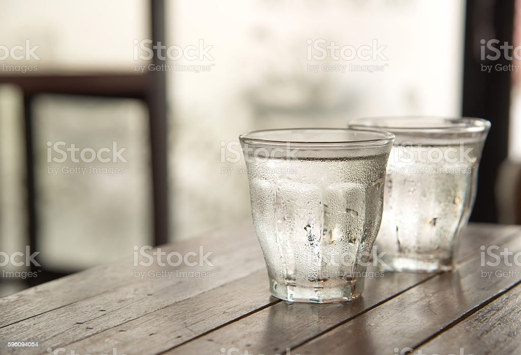 Glass water on wooden table with poor light background. royalty-free stock photo
