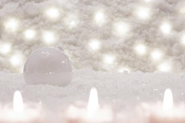 glass white ball is in the snow. - weihnachtsspende stock-fotos und bilder