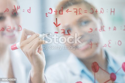 499203366 istock photo A glass whiteboard is being used to brainstorm lab experiment data 858045838