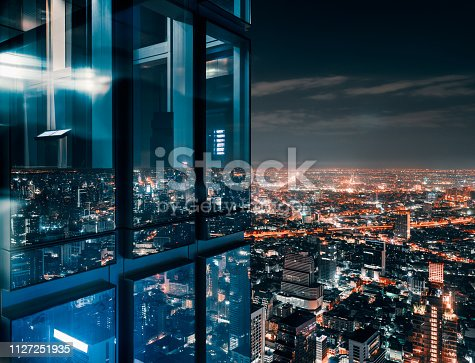 Corner glass window with glowing crowded city