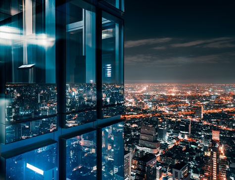 Glass window with glowing crowded city