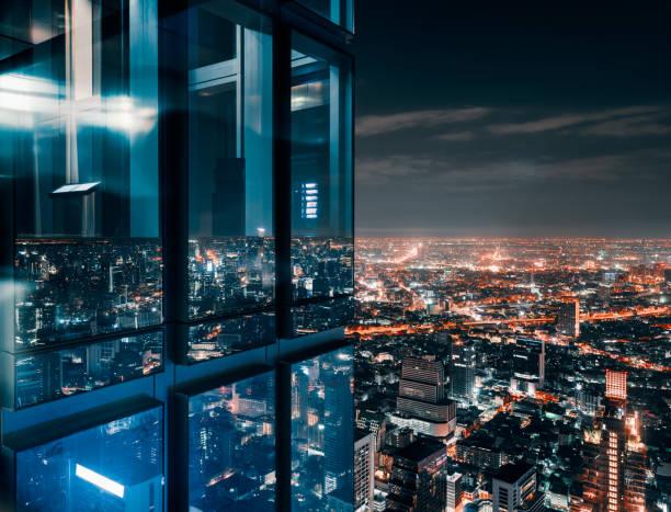 janela de vidro com brilhante cidade aglomerada - arranha céu - fotografias e filmes do acervo
