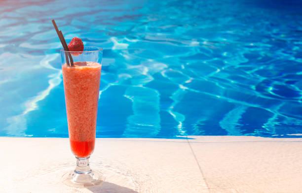 Vidrio con un cóctel rojo brillante en la mesa junto a la piscina con espacio de copia - foto de stock