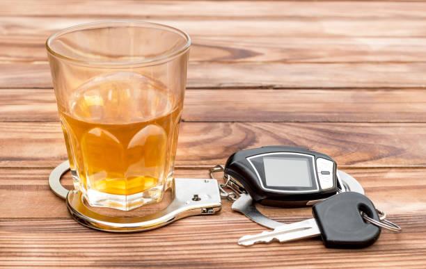 glas mit alkoholischen getränk, handschellen und auto schlüssel auf holztisch. - whisky test stock-fotos und bilder