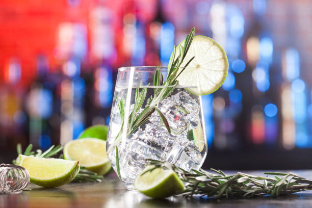 Glass with alcoholic drink with lime, ice and rosemary stock photo