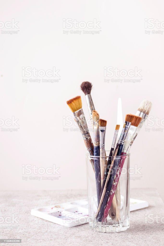 Vidrio con pinceles artísticos y paleta de mesa gris - foto de stock